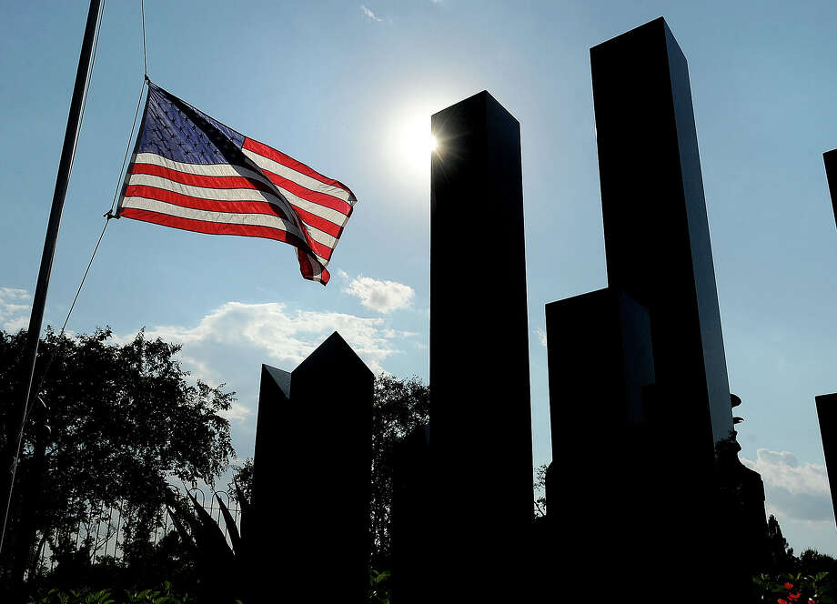 An American flag flies at half staff next to a twin towers statue at Tyrrell Park in Beaumont in 2011. Guiseppe Barranco/The Enterprise Photo: Guiseppe Barranco