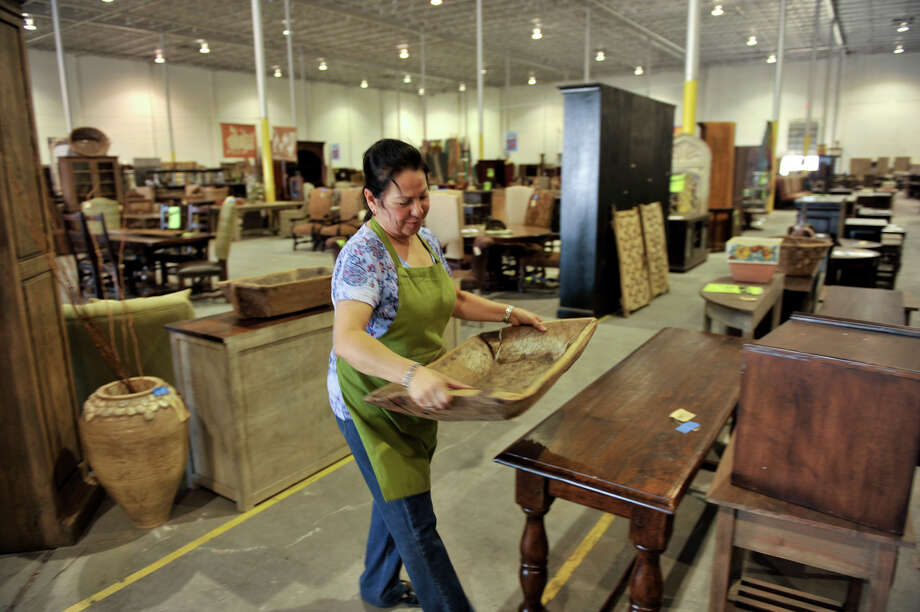 SLUG: Armoire expansion 0911-AssignID 445408-September 10, 2012-San Antonio, Texas---Armoires and Accents employee Maggie Lopez moves a large bowl at the company's new warehouse outlet store for home furnishings at 9311 Broadway. Photo: For The Express-News