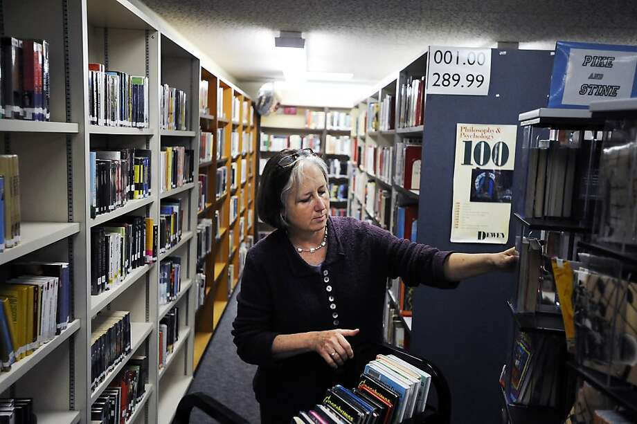 Carla Colburn, the former full-time librarian, prepares a book cart for students in the Logan High library. Photo: Michael Short, Special To The Chronicle