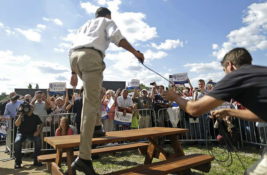Mitt Romney climbs on a picnic table to address supporters in Mansfield, Ohio. Photo: Charles Dharapak, Associated Press