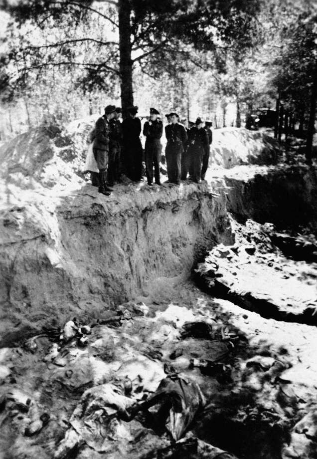 FILE - This Feb. 4, 1952, photo, shows a view of a partially emptied mass grave in the Katyn forest where a massacre of some 10,000 Polish prisoners of war took place in May 1943, near Smolensk, Russia.  Col. John H. van Vliet is shown in the group at the edge of the trench, and van Vliet is convinced that the Russians, not the Germans, were responsible for the massacre. The Obama administration is opposing a Jewish group's bid to levy civil fines against Russia for failing to obey a court order to return its historic books and documents ? a dispute which has halted the loan of Russian art works for exhibit in the United States. In a recent court filing, the Justice Department argued that judicial sanctions against Russia in this case would be contrary to U.S. foreign policy interests and inconsistent with U.S. law. The Jewish group, Chabad-Lubavitch of Brooklyn, N.Y., has already persuaded Chief Judge Royce Lamberth of the U.S. District Court here that it has a valid claim to the tens of thousands of religious books and manuscripts, some up to 500 years old, which record the group's core teachings and traditions.  (AP Photo) / AP