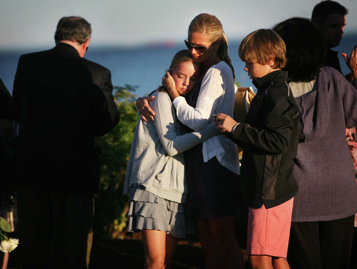 Sophie Pelletier-Martinelli, widow of 9/11 victim Michael Pelletier, hugs her daughter Sydney, 13, at the annual memorial service at Sherwood Island State Park in Westport on Monday, September 10, 2012. At right is Pelletier-Martinelli's son Nicolas, 11.