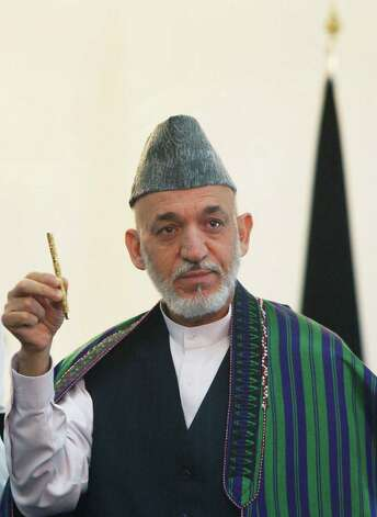 Afghan President Hamid Karzai holds a pen which belonged to former Afghanistan King Shah Amanullah Khan, who ruled the country from 1919, to 1929, during a ceremony where he received the pen from the King's daughter, Princess India of Afghanistan, at the presidential palace in Kabul, Afghanistan, Monday, Aug. 27, 2012. The pen will be transferred to the Afghan National Museum. (AP Photo/Ahmad Massoud /Xinhua, Pool) Photo: Ahmad Massoud / Xinhua Pool