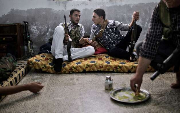 A Syrian rebel fighter, right, eats while others chat as they wait for transportation to go and fight government forces in Aleppo, at their headquarters in Suran, on the outskirts of Aleppo, Syria, Monday, Sept. 10, 2012. (AP Photo/Muhammed Muheisen) Photo: Muhammed Muheisen