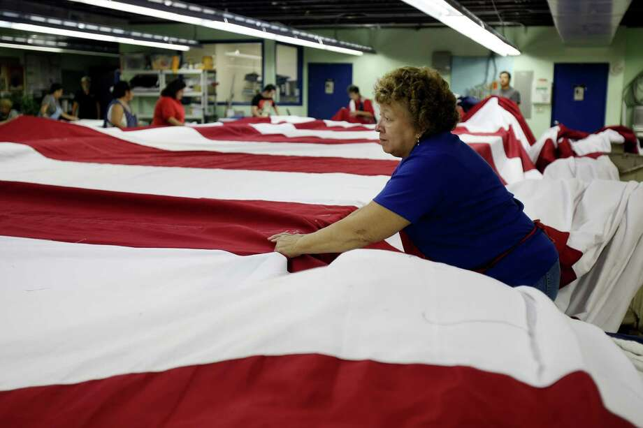 Josie Sanchez helps fold a huge American flag created by the Dixie Flag Manufacturing Co. for Tuesday's World Trade Center Memorial dedication ceremony. Photo: Helen L. Montoya / SAN ANTONIO EXPRESS-NEWS