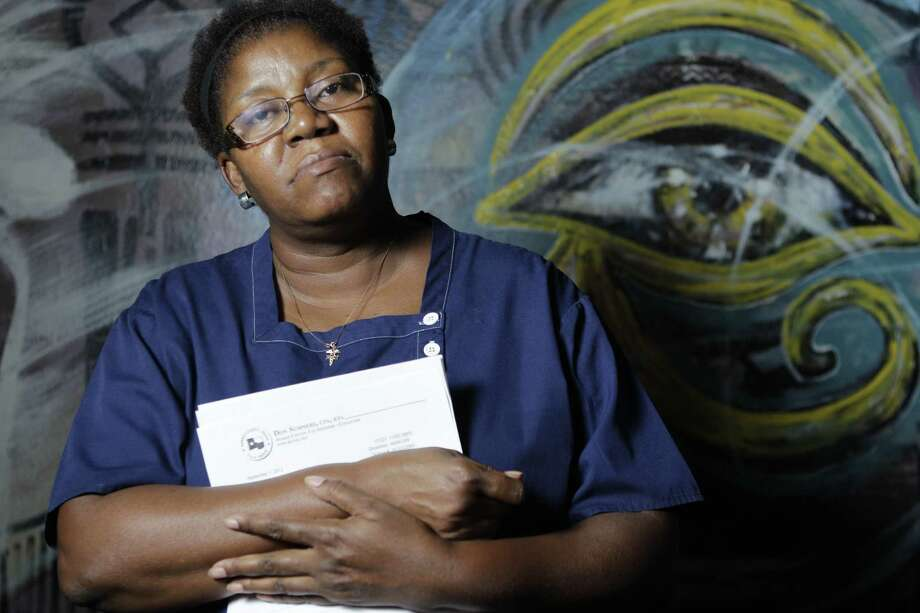 Terri Collins holds a letter from the county tax office saying it has learned that she is dead and will be taken off the voter registration record. Just a month earlier, she received her voter registration ID card. The voter purge was cancelled after complaints. Photo: Melissa Phillip / © 2012 Houston Chronicle