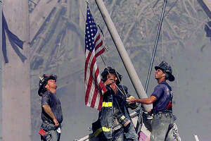 RETRANSMISSION TO ADD IDENTIFICATION OF FIREFIGHTERS--Brooklyn firefighters George Johnson, left, of ladder 157, Dan McWilliams, center, of ladder 157, and Billy Eisengrein, right, of Rescue 2, raise a flag at the World Trade Center in New York Tuesday, Sept. 11, 2001, as work at the site continues after hijackers crashed two airliners into the center. (AP Photo/The Record, Thomas E. Franklin) MANDATORY CREDIT