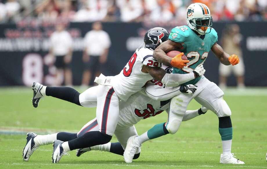 Dolphins running back Reggie Bush (22) exposed a weak link in the Texans' defense Sunday, averaging 4.9 yards per carry. The Dolphins averaged 4.2. Photo: Karen Warren / © 2012  Houston Chronicle
