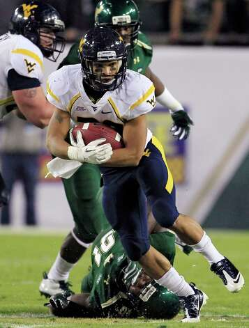 West Virginia running back Dustin Garrison (29) cuts past South Florida defensive tackle Keith McCaskill (91) during the first quarter of an NCAA college football game, Thursday, Dec. 1, 2011, in Tampa, Fla. (AP Photo/Chris O'Meara) Photo: Chris O'Meara, Associated Press / AP