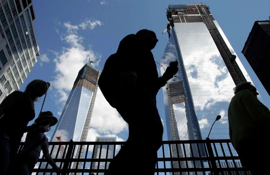 Visitors to the National September 11 Memorial walk below the rising towers 1 World Trade Center, left, and 4 World Trade Center, Monday, Sept. 10, 2012 in New York. Tuesday will mark the eleventh anniversary of the attacks of Sept. 11, 2001. (AP Photo/Mark Lennihan) Photo: Mark Lennihan