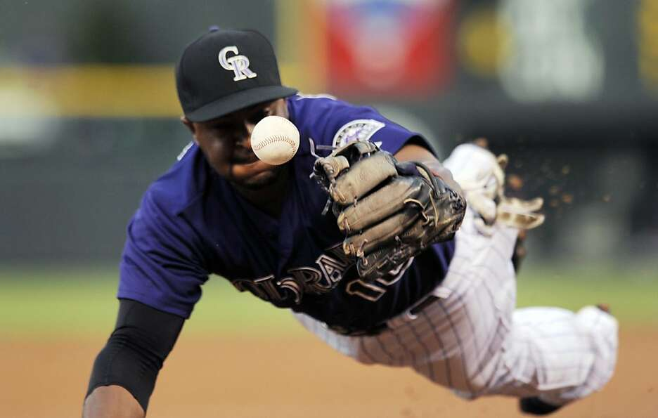 Colorado Rockies third baseman Chris Nelson knocks down a line drive by San Francisco Giants Marco S