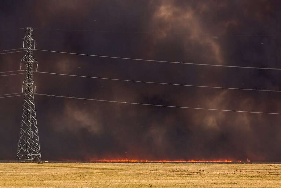 Grass fire spreads across the Blood Reserve near Highway 509 west of Lethbridge, Alberta on Monday Sept. 10, 2012. A rapidly moving grass fire in southern Alberta has prompted officials to order everyone in a town southeast of Calgary to evacuate. (AP Photo/The Canadian Press, Jaime Vedres) Photo: Jaime Vedres, Associated Press
