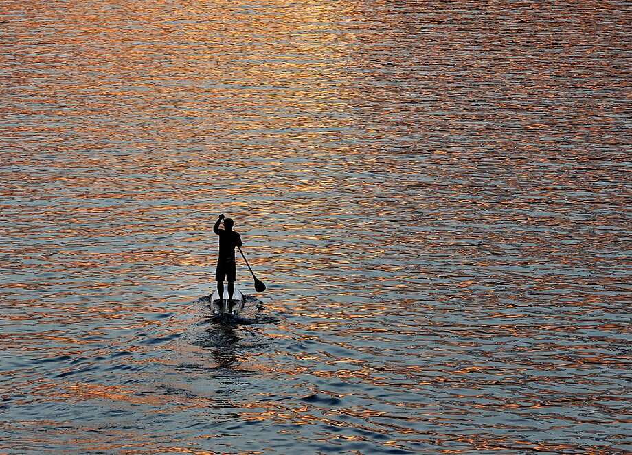 A man paddles on the Main river as the sun sets in Frankfurt, Germany, Monday, Sept. 10, 2012. (AP Photo/Michael Probst) Photo: Michael Probst, Associated Press