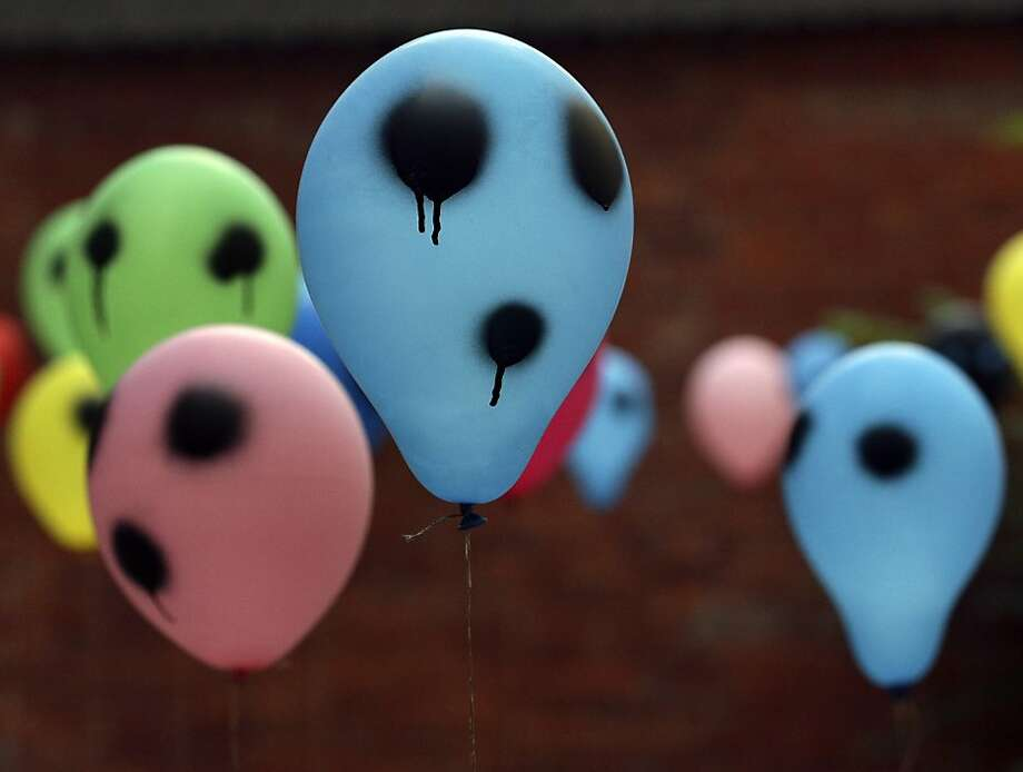 Balloons painted by a woman who introduced herself as Russian artist Margo Trushina, unseen, are displayed during an art performance at a former women's prison to support the Russian punk band 'Pussy Riot' in Berlin, Germany, Monday, Sept. 10, 2012. (AP Photo/Michael Sohn) Photo: Michael Sohn, Associated Press
