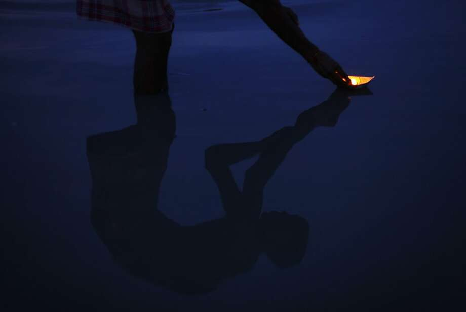 In this Sunday, Sept. 9, 2012 photo, an Indian Hindu devotee, reflected on water, offers an oil lamp as he performs evening rituals in the River Ganges in Allahabad, India. Allahabad, on the confluence of the rivers Ganges and Yamuna, is one of Hinduism's important centers. (AP Photo/Rajesh Kumar Singh) Photo: Rajesh Kumar Singh, Associated Press