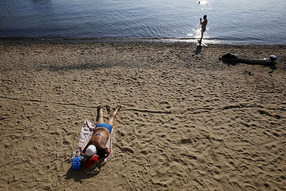 A woman sunbathes on a beach in Vladivostok, Russia, Monday, Sept. 10, 2012. (AP Photo/Greg Baker) Photo: Greg Baker, Associated Press