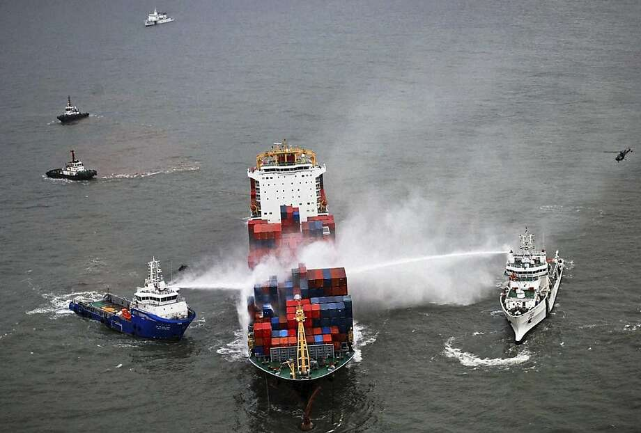Indian coast guard vessels perform cooling operations after a major fire broke out on the Colombo-bound merchant vessel M V Amsterdam, center, on the Arabian Sea off the coast of Mumbai, India, Monday, Sept. 10, 2012. According to local news reports, the ship, carrying hazardous cargo, caught fire Sunday. (AP Photo) Photo: Associated Press