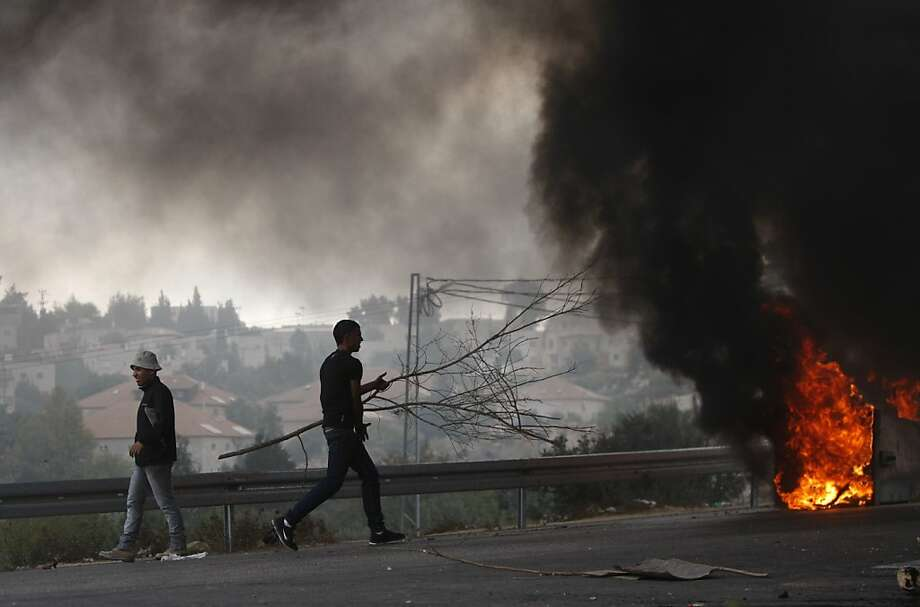 Palestinian youths burn tires during a protest against the high cost of living at the Jilazoun refugee camp in the West Bank city of Ramallah, Monday, Sept. 10, 2012. The Palestinian Authority, which governs Palestinians in the West Bank, is suffering a budgetary shortfall because the U.S. and Arab countries that sustain it haven't paid all the aid money that they have promised. (AP Photo/Majdi Mohammed) Photo: Majdi Mohammed, Associated Press
