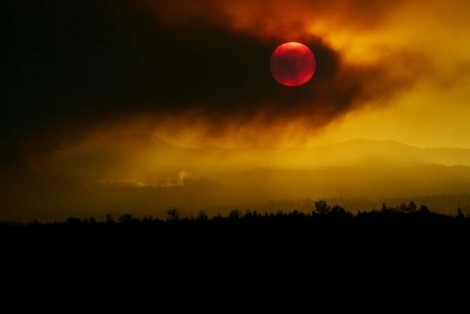 In this Sunday, Sept. 9, 2012 photo, smoke from the Pole Creek Fire obscures the sun near Sisters, Ore., at sunset. The wildfire, burning in heavy downed and dead material just southwest of Sisters, Ore., is estimated to be near 2,000 acres. (AP Photo/The Bulletin, Rob Kerr) Photo: Rob Kerr, Associated Press