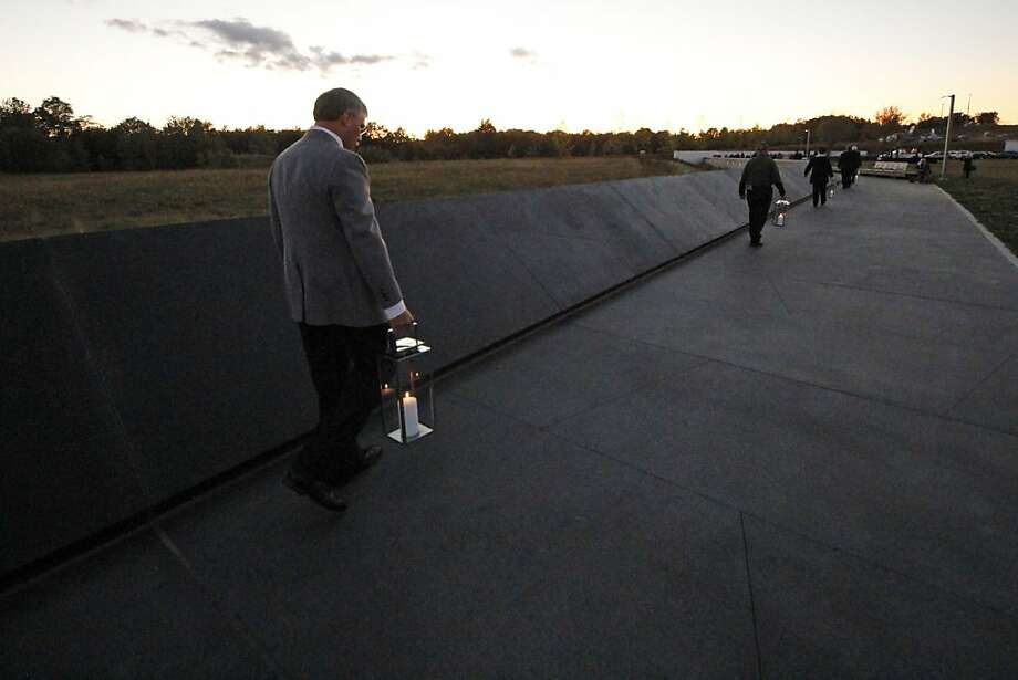 Forty luminaria are carried to the wall of names in memory of the 40 passengers and crew of United Flight 93 at the Flight 93 National Memorial at sunset on Monday, Sept. 10, 2012 in Shanksville, Pa. (AP Photo/Gene J. Puskar) Photo: Gene J. Puskar, Associated Press