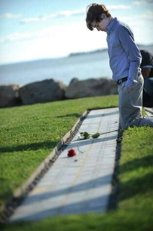 Christopher Gardner, 14, of Darien, kneels at his father's memorial stone at ConnecticutâÄôs 9/11 Living Memorial during the 11th Annual 9/11 Memorial Service held Monday, September 10, 2012 at Sherwood Island State Park in Westport, Conn.  His father, Christopher Samuel Gardner, worked at the World trade center and died on 9/11. Photo: Autumn Driscoll / Connecticut Post