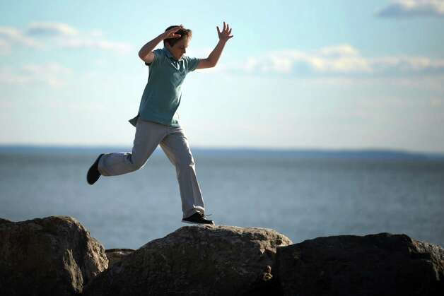 Twelve-year-old Joseph Lenihan, of Greenwich, leaps across rocks before the 11th annual 9/11 Memorial Service Monday, September 10, 2012 at Sherwood Island State Park in Westport, Conn. His father, Joseph Anthony Lenihan, was killed in the Sept. 11, 2001 terrorist attacks. Photo: Autumn Driscoll / Connecticut Post