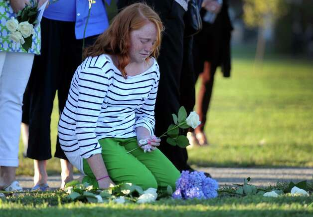 Emma Hunt, 12, of Essex, places flowers on her father's name at ConnecticutâÄôs 9/11 Living Memorial during the 11th annual 9/11 Memorial Service Monday, September 10, 2012 at Sherwood Island State Park in Westport, Conn. William Christopher Hunt, of Norwalk, died in 2 Tower World Trade Center. Photo: Autumn Driscoll / Connecticut Post