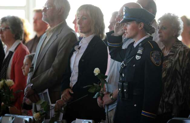 Alex Blackwell, a Madison police officer, salutes during ConnecticutâÄôs 11th Annual 9/11 Memorial Service Monday, September 10, 2012 at Sherwood Island State Park in Westport, Conn.   Blackwell lost her father, Chris Blackwell, on 9/11. Photo: Autumn Driscoll / Connecticut Post