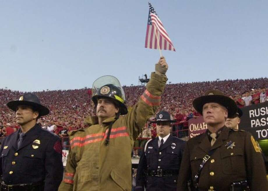 An unidentified fire fighter holds a flag high during the opening ceremony of the Nebraska-Rice University football game held at Memorial Stadium in Lincoln, Neb., Thursday Sept. 20, 2001.  (AP Photo/Dave Weaver) (DAVE WEAVER / ASSOCIATED PRESS)