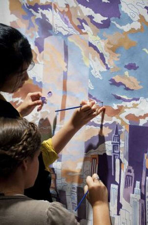Jessica Huynh, top, and Alana Roecker brush in the colors of a paint-by-number canvas of the original World Trade Center towers, at a news conference, Monday, Sept. 10, 2012 in New York. On the eve of the Sept. 11 anniversary, the faces and recorded voices of those who died have been unveiled as part of the future 9/11 Memorial Museum. (AP Photo/Mark Lennihan) (Mark Lennihan / Associated Press)