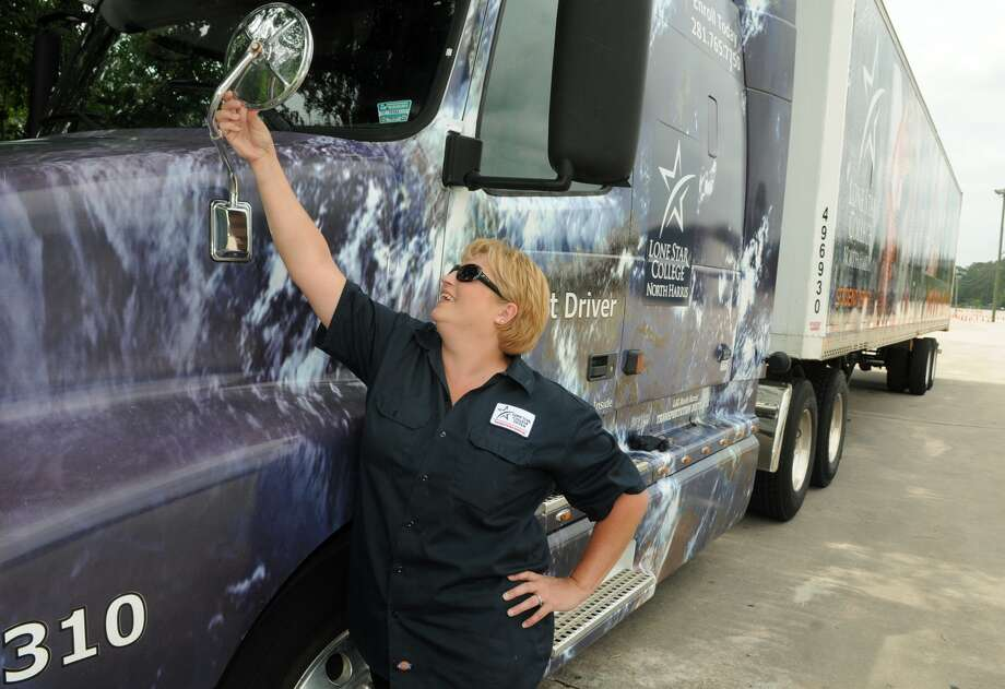 Kristy Cox, of Cypress, who recently graduated from the Lone Star College System's Professional Truck Driver program, adjusts an outside mirror on one of the school's trucks. Photo: Jerry Baker