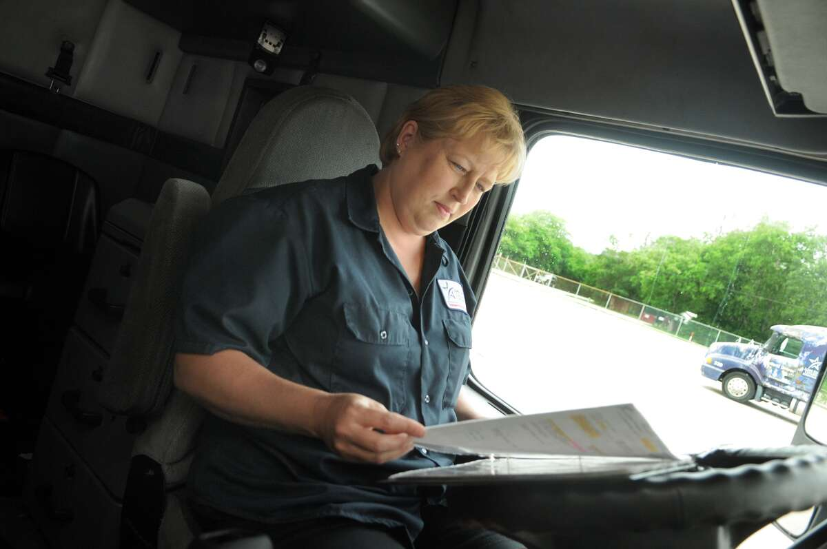 Kristy Cox checks the pre-trip book inside the cab of one of the trucks at the Lone Star College System's truck driving school.