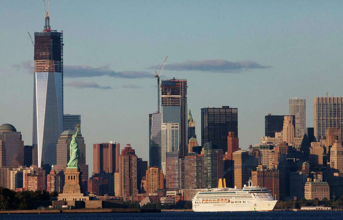 A cruise ship passes the World Trade Center in New York and the Statue of Liberty, left, on Monday, Sept. 10, 2012 in this photo taken from Bayonne, N.J. The tallest tower is 1 World Trade Center, now up to 104 floors, and in the center is 4 World Trade Center, also under construction. The tallest tower, Freedom Tower, will be 1,776 feet tall, including its spire, a reference to the year of American independence.