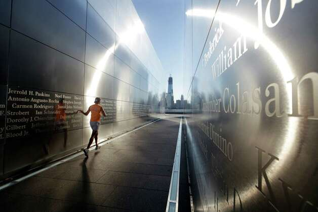 The construction of One World Trade Center, now up to 104 floors, is seen Tuesday, Sept. 11, 2012, across the Hudson River as a runner glides his hand at Liberty State Park in Jersey City, N.J.,  along the wall of 'Empty Sky,' New Jersey's memorial to the 749 people from the state lost during the  Sept. 11 terrorist attacks on the World Trade Center.  Americans paused again Tuesday to mark the 11th anniversary of the Sept. 11, 2001, terror attacks with familiar ceremonies, but also a sense that it's time to move forward after a decade of remembrance. Photo: Mel Evans / Associated Press