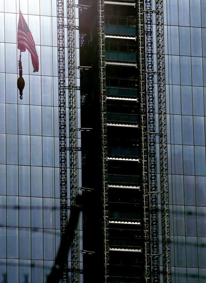 A United States flag hangs from a crane on the side of the construction site of One World Trade Center. Photo: Julio Cortez / Associated Press