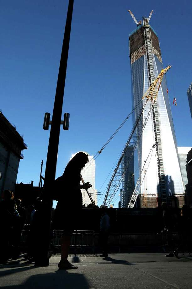 People walk near the construction site of One World Trade Center during the 11th anniversary of the Sept. 11 terrorist attacks, Tuesday, Sept. 11, 2012, in New York. As in past years, thousands were expected to gather at the World Trade Center site in New York, the Pentagon and Shanksville, Pennsylvania, to read the names of nearly 3,000 victims killed in the worst terror attack in U.S. history. Photo: Julio Cortez / Associated Press