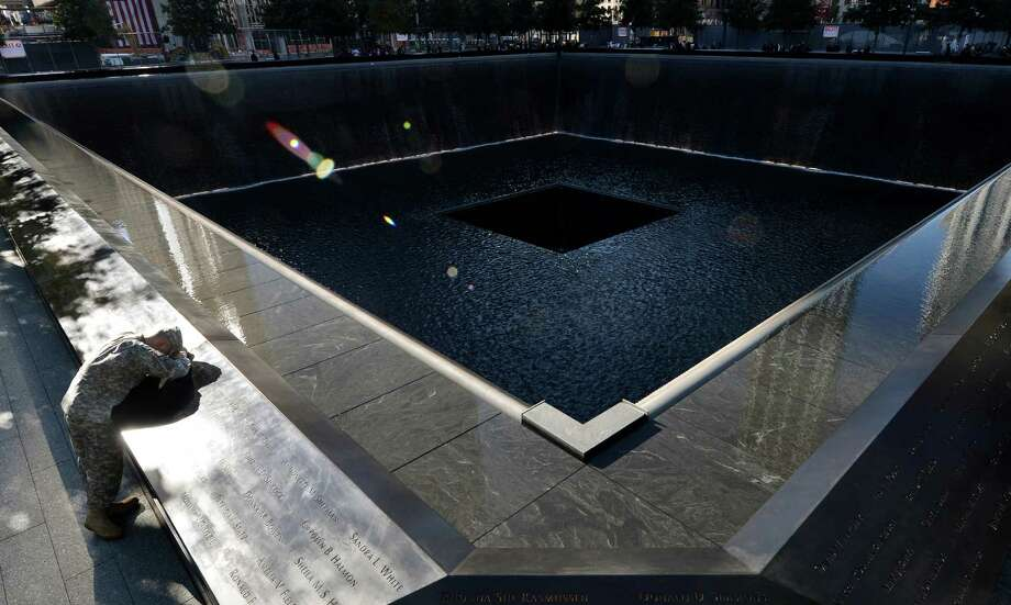 Scott Willens, who joined the United States Army three days after the attacks on Sept. 11, 2001, pauses by the South Pool of the World Trade Center Memorial during the 11th anniversary observance,Tuesday Sept. 11, 2012 in New York. (AP Photo/Justin Lane, Pool, EPA Photo: Justin Lane / Associated Press