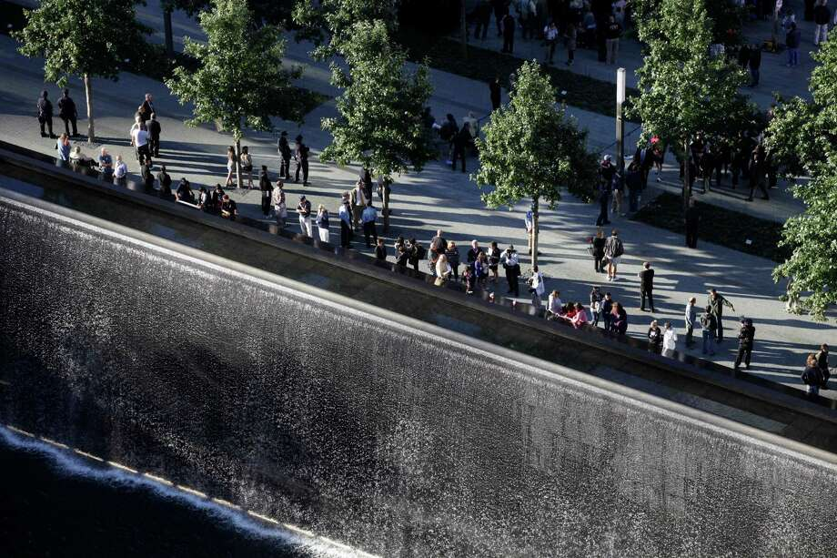 Friends and families of victims of the Sept. 11, 2001, terror attacks, look over a reflecting pool during a ceremony at the National September 11 Memorial, Tuesday, Sept. 11, 2012 in New York. As in past years, thousands are expected to gather at the World Trade Center site in New York, the Pentagon and Shanksville, Pennsylvania, to read the names of nearly 3,000 victims killed in the worst terror attack in U.S. history. Photo: Mark Lennihan / Associated Press