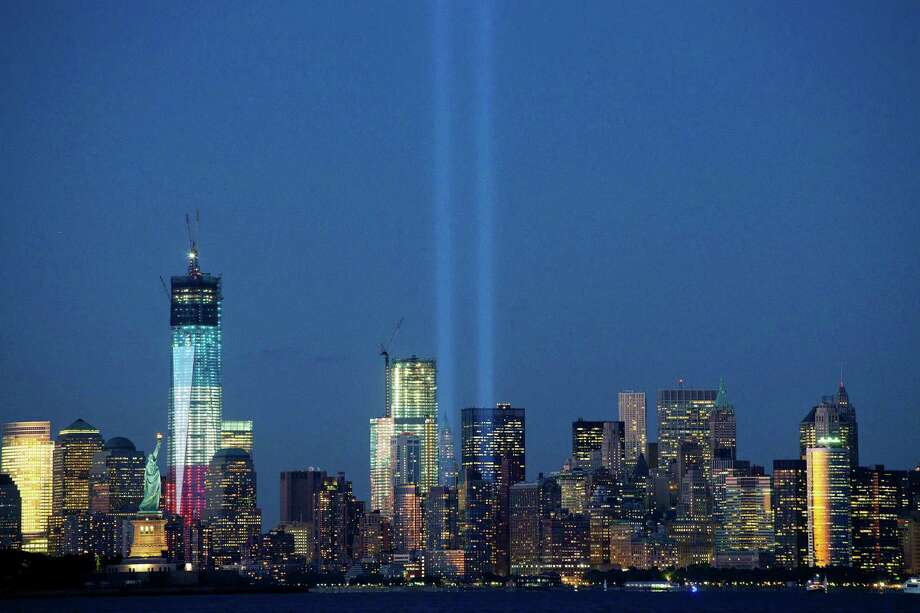 The Tribute in Light shines above the World Trade Center in New York and the Statue of Liberty, left, Monday, Sept. 10, 2012 in this photo taken from Bayonne, N.J. Tuesday will mark the eleventh anniversary of the terrorist attacks of Sept. 11, 2001.  The tallest tower is 1 World Trade Center, now up to 105 floors. In the center is 4 World Trade Center. Photo: Mark Lennihan / Associated Press