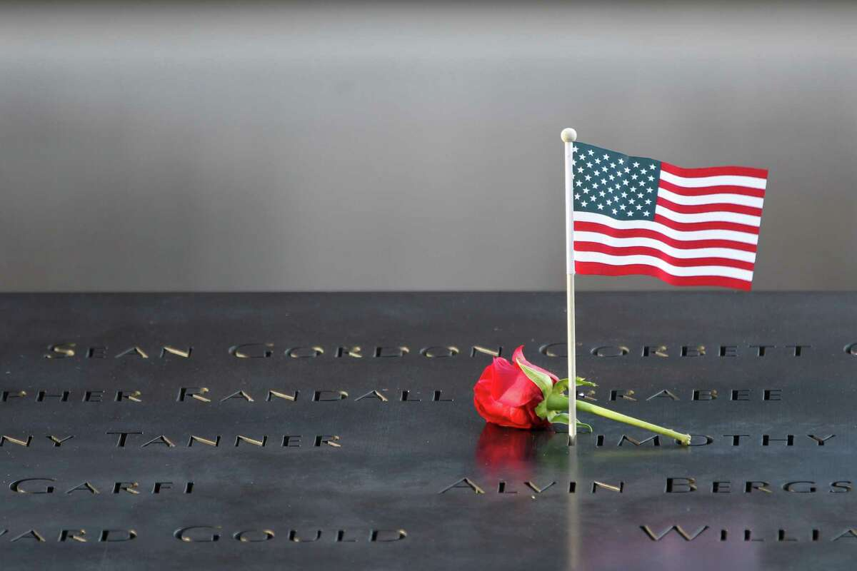 A flower and an American flag are placed next to the names inscribed on the edge of the memorial pool during the observances held on the eleventh anniversary of the attacks on the World Trade Center, September 11, 2012 in New York. AFP Photo Mary Altaffer-PoolMARY ALTAFFER/AFP/GettyImages