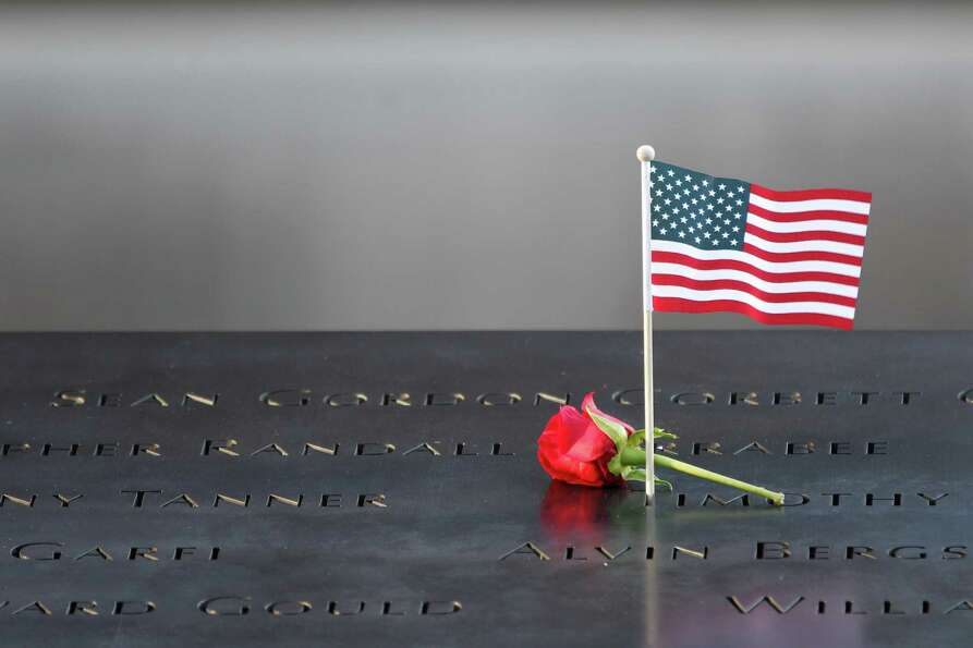 A flower and an American flag are placed next to  the names inscribed on the edge of the memorial po