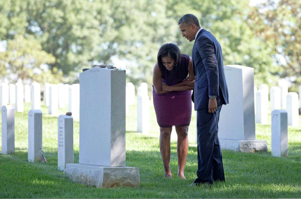 President Barack Obama and first lady Michelle Obama visit Section 60, placing Challenge Coins on tombstones, Tuesday, Sept. 11, 2012, at Arlington National Cemetery in Arlington, on the 11th anniversary of the 9/11 attacks.