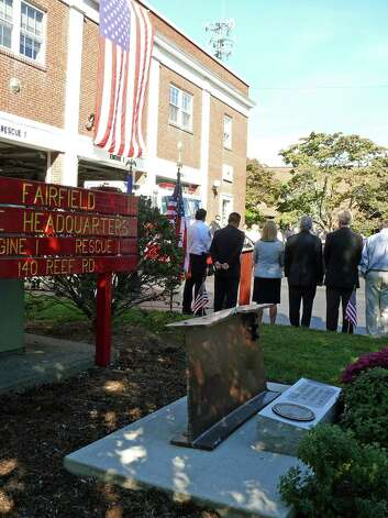 Offcials take part in the annual ceremony at fire headquarters honoring those killed in the Sept. 11 terrorist attacks. In the foreground is a memorial made with a steel beam from the World Trade Center. Photo: Genevieve Reilly / Fairfield Citizen