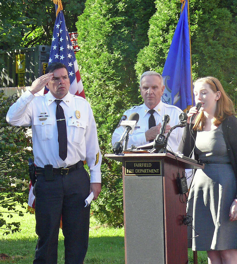 Police Chief Gary MacNamara, left, and Fire Chief Richard Felner stand at attention while Fairfield Warde High School student Lindsey Reuter sings the National Anthem during ceremonies Tuesday marking the 11th anniversary of the Sept. 11 terrorist attacks.. Photo: Genevieve Reilly / Fairfield Citizen