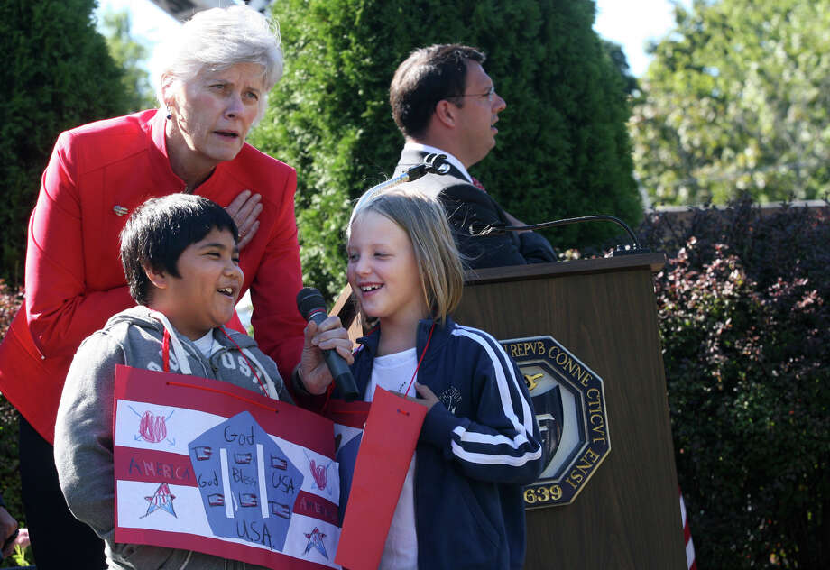 Milford superintendent of Schools Dr. Elizabeth Fesser holds the microphone for second graders, Luke Cruz and Savannah Obymachow while they recite the Pledge of Allegiance during a 9/11 remembrance ceremony at Live Oaks School in Milford, Conn. on Monday. September 11, 2012. Photo: B.K. Angeletti / Connecticut Post freelance B.K. Angeletti