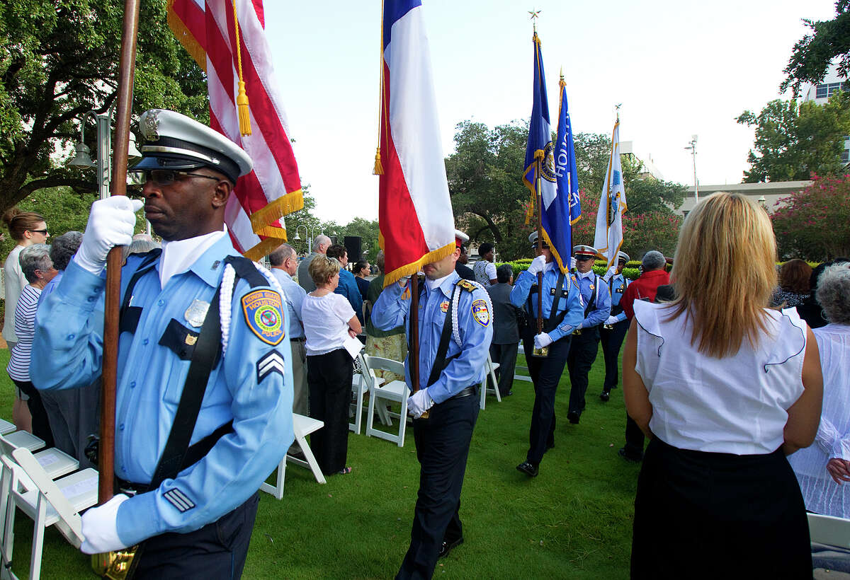 A Houston Fire Department and police honor guard presents the colors Tuesday at Market Square Park.