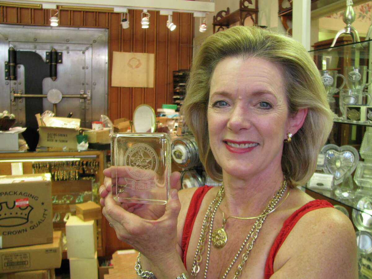 Laurel Wendt holds a paperweight that features the flag she designed for the city's 175th anniversary.