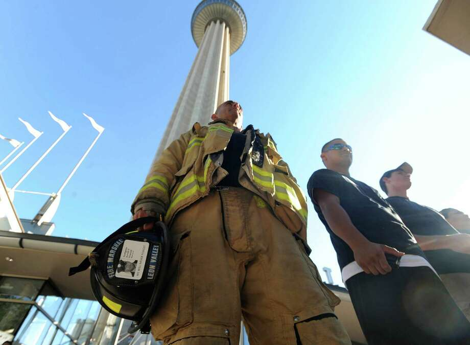 Fire Marshal Luis Valdez of Leon Valley stands by the Tower of the Americas, which he and others climbed, during the 9/11 Patriot Day Tower Ascent on Sept. 11, 2012. Participants climbed the Tower of the Americas -- some twice, to equal the height of the 110 floors of the World Trade Center. The event was sponsored by the Family Education Alliance of South Texas. Photo: Billy Calzada, San Antonio Express-News / © San Antonio Express-News