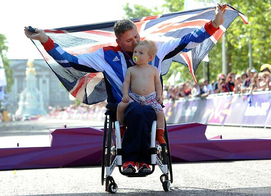 Marathon man:Great Britain's David Weir holds the Union Jack as  he celebrates his gold medal win at the London Paralympics with his son,  Mason. Weir finished first in the men's Marathon T54. Photo: Paul Ellis, AFP/Getty Images