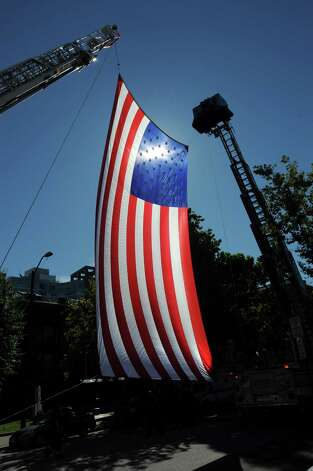 A huge flag hung outside the Margaret E. Morton Government Center in Bridgeport, Conn. on Tuesday, Sept. 11, 2012.  Mayor Bill Finch, Fire Chief Brian Rooney and Police Chief Joseph L. Gaudett took part in a ceremony to mark the 11th anniversary of the terrorist attacks on Sept. 11, 2001. Photo: Cathy Zuraw / Connecticut Post